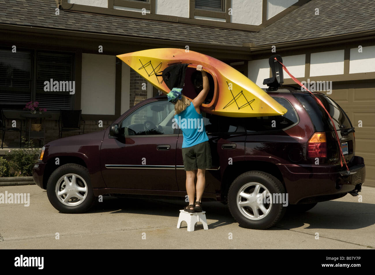 Woman Using Steps To Load Kayak To Roof Rack Of Suv On Driveway