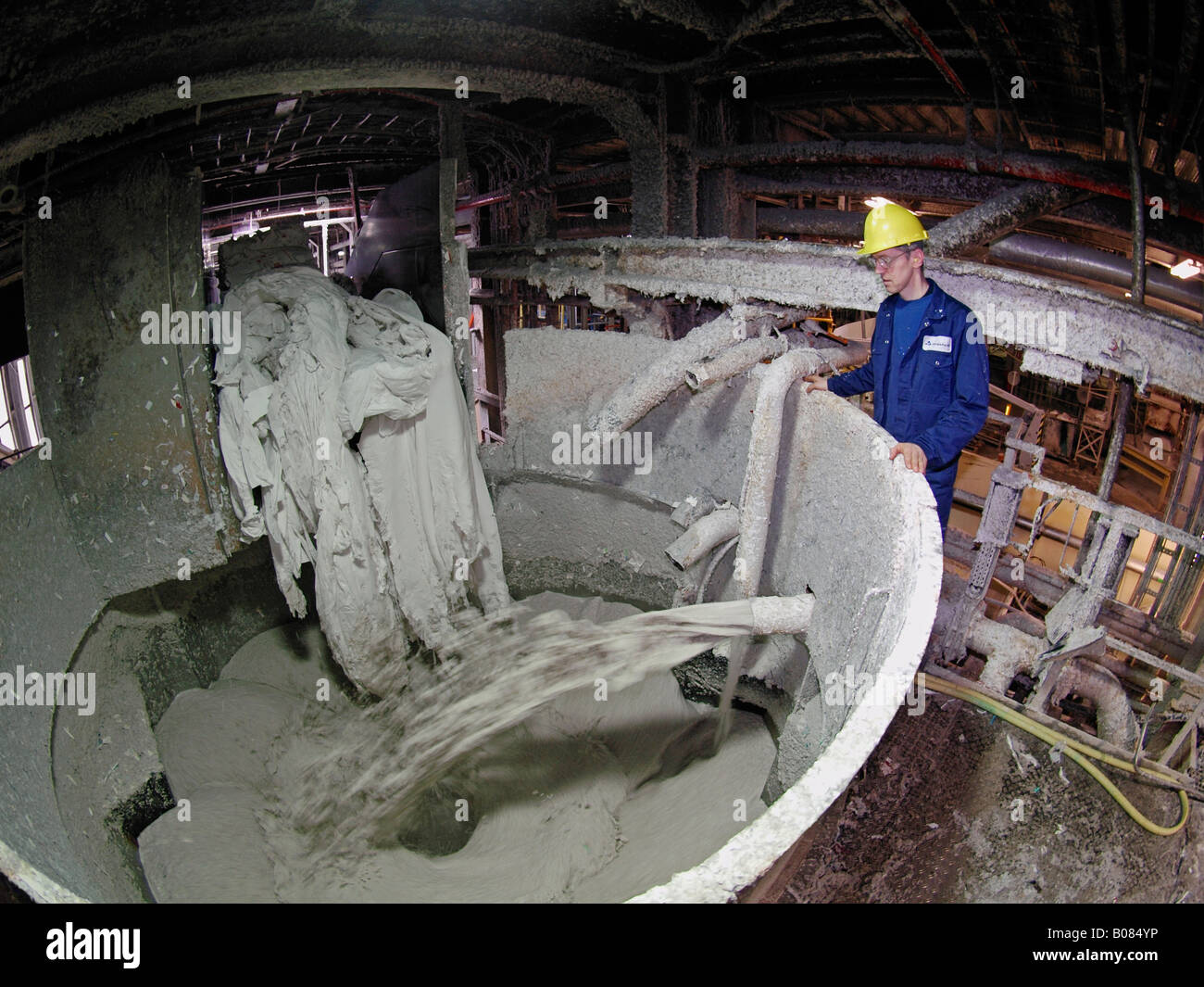 Man Standing Next To Large Machine Where Old Waste Paper
