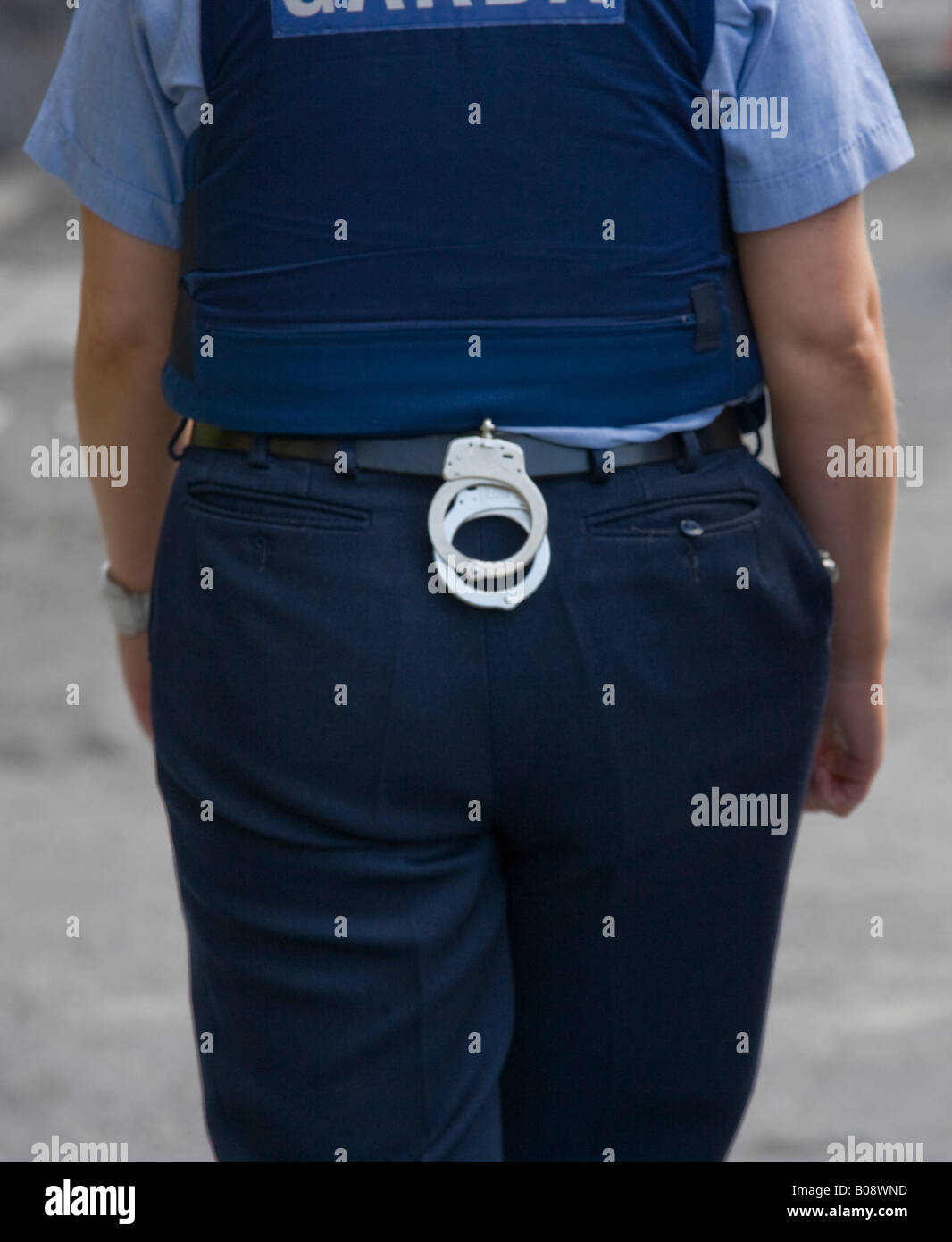 rear view of police woman with a pair of handcuffs on her belt