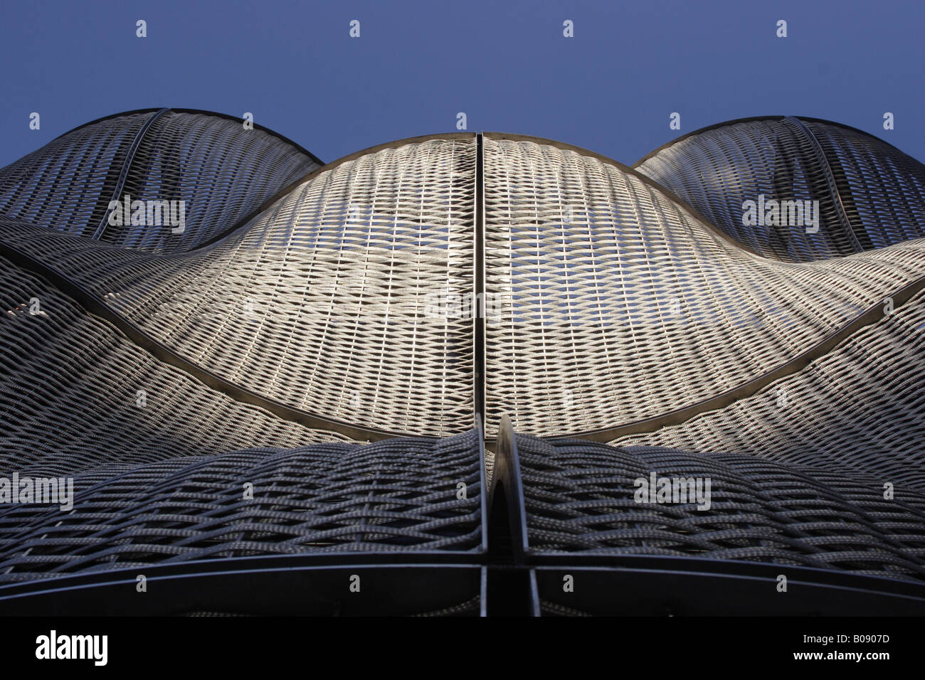 Waves Of An Architectural Cladding Of A Steel Weave At Dusk Stock - Architectural cladding