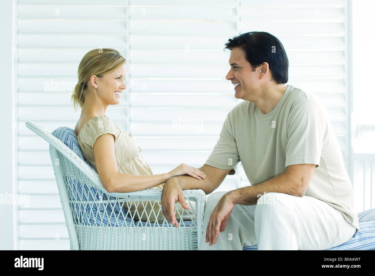 Couple sitting face to face on porch, smiling, woman