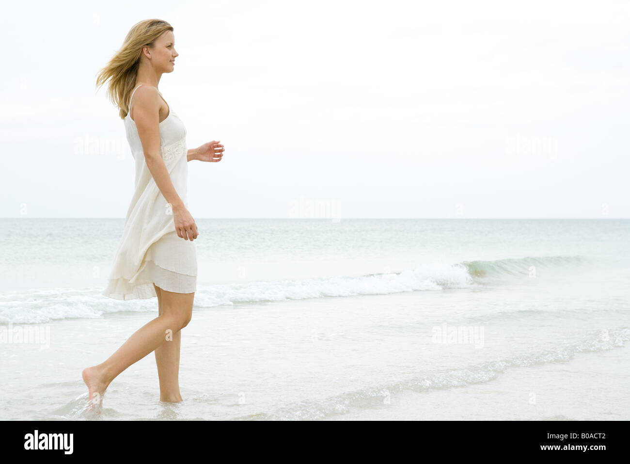 Woman walking on a beach royalty - Woman Walking At The Beach Side View
