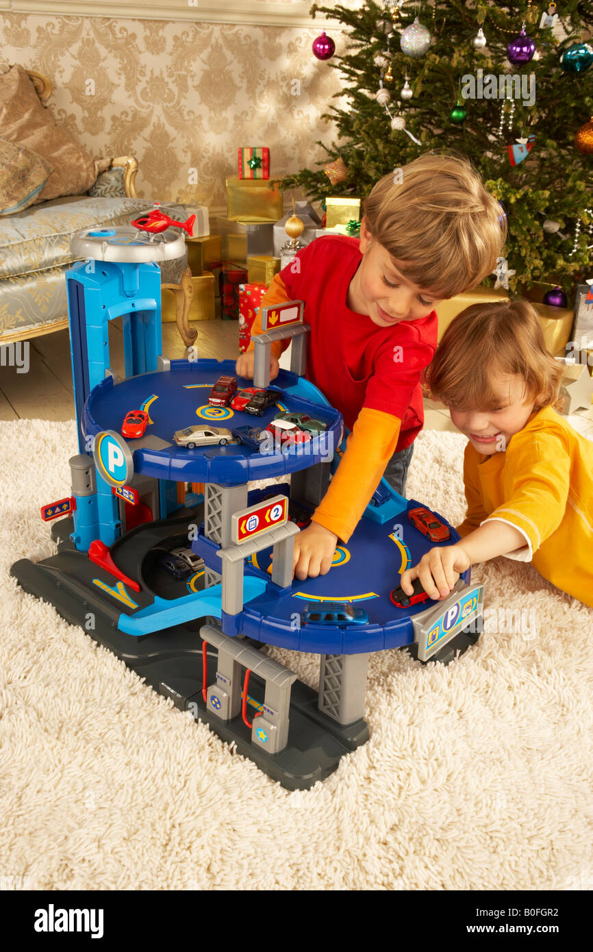 Toys For Boys Under 2 : Two boys play at christmas time under the tree with a toy