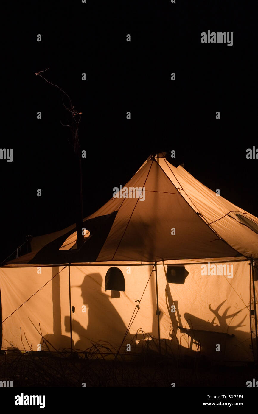 Silhouettes outline a hunter when a lantern lights up a wall tent at hunting c& at night. MR & Silhouettes outline a hunter when a lantern lights up a wall tent ...