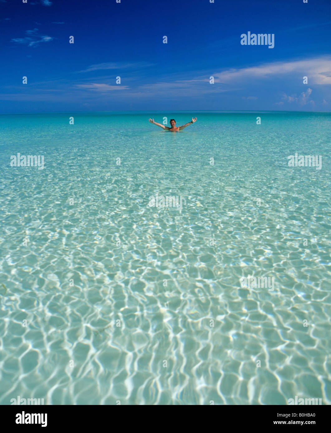 crystal clear ocean water man standing in shallow water