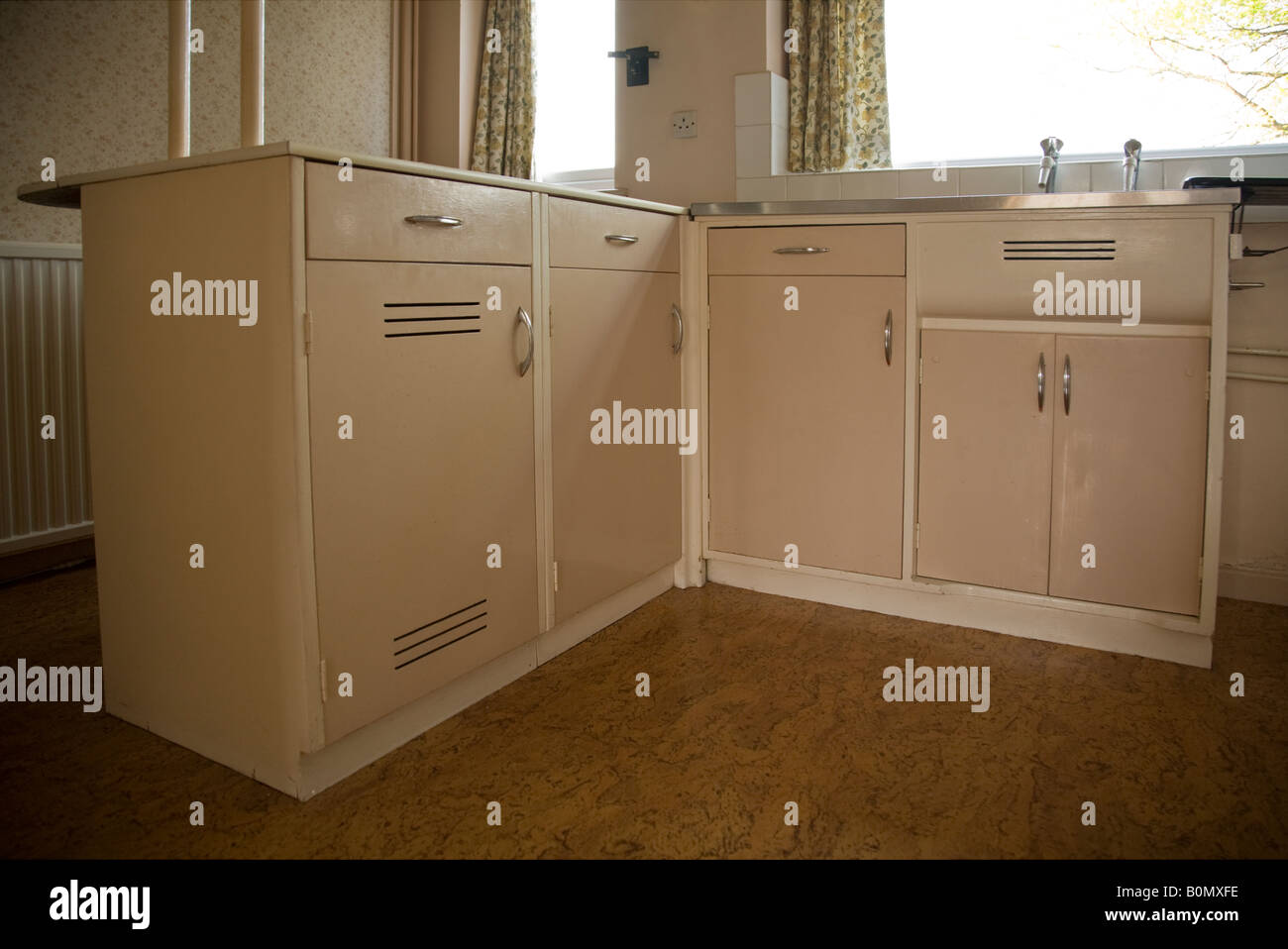 Old fashioned fitted cupboards in a domestic 1950s kitchen for Fitted kitchen cupboards