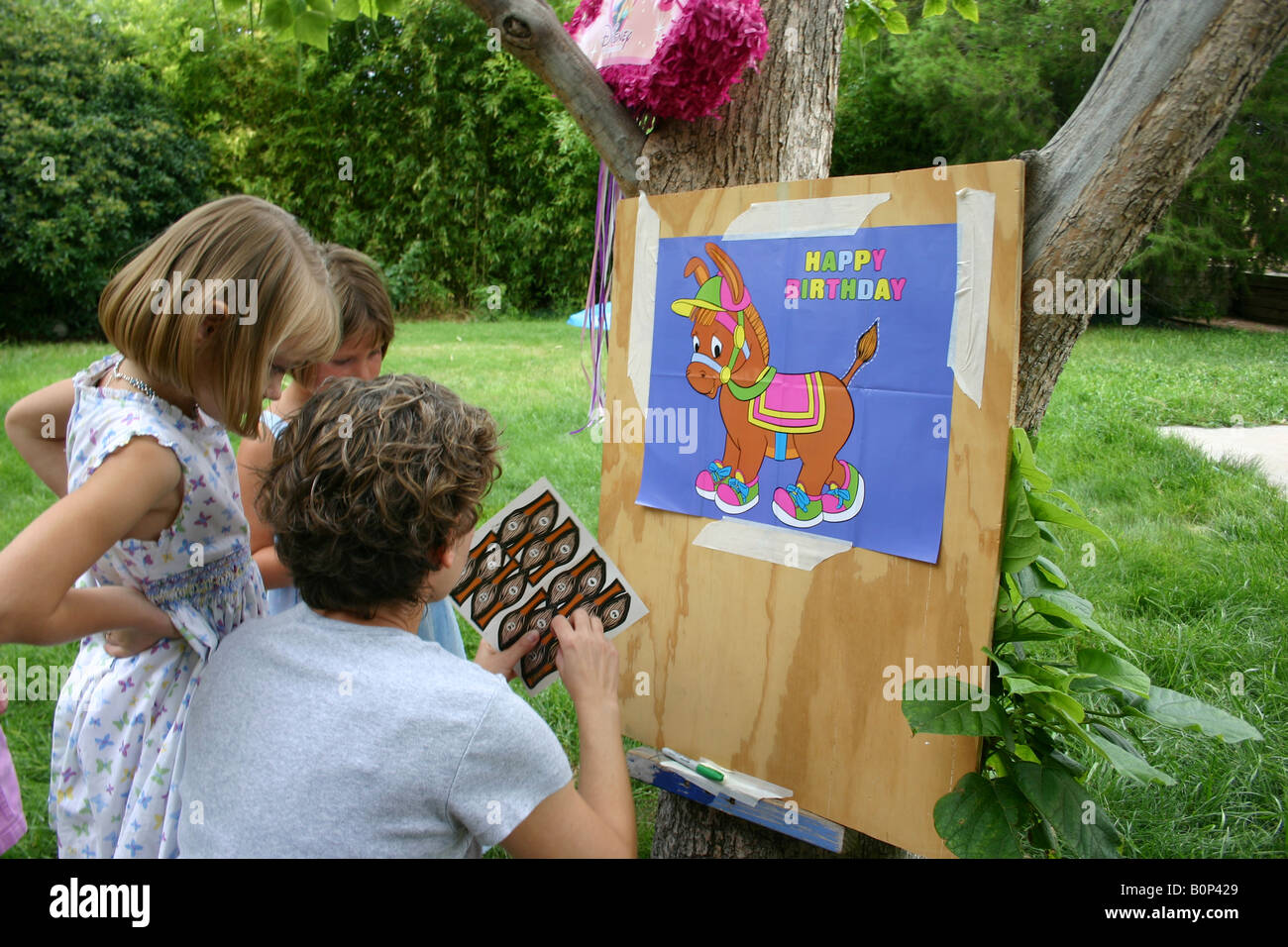 Child And Parent Setting Up Birthday Party Game Pin The Tail On Donkey In Backyard