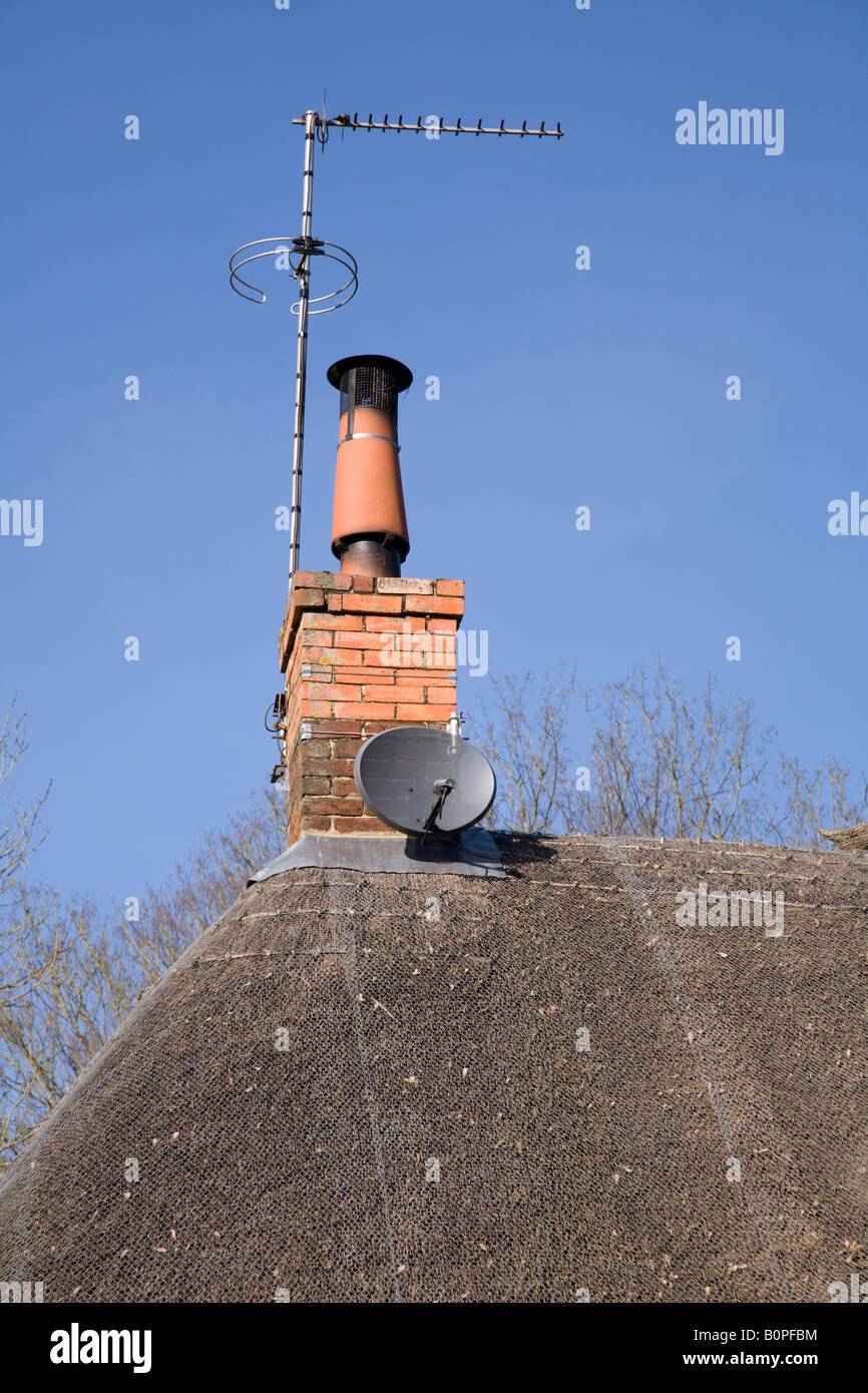 Satellite Dish On A Thatched Roof Alongside A Chimney Mounted TV Ariel  Antenna.