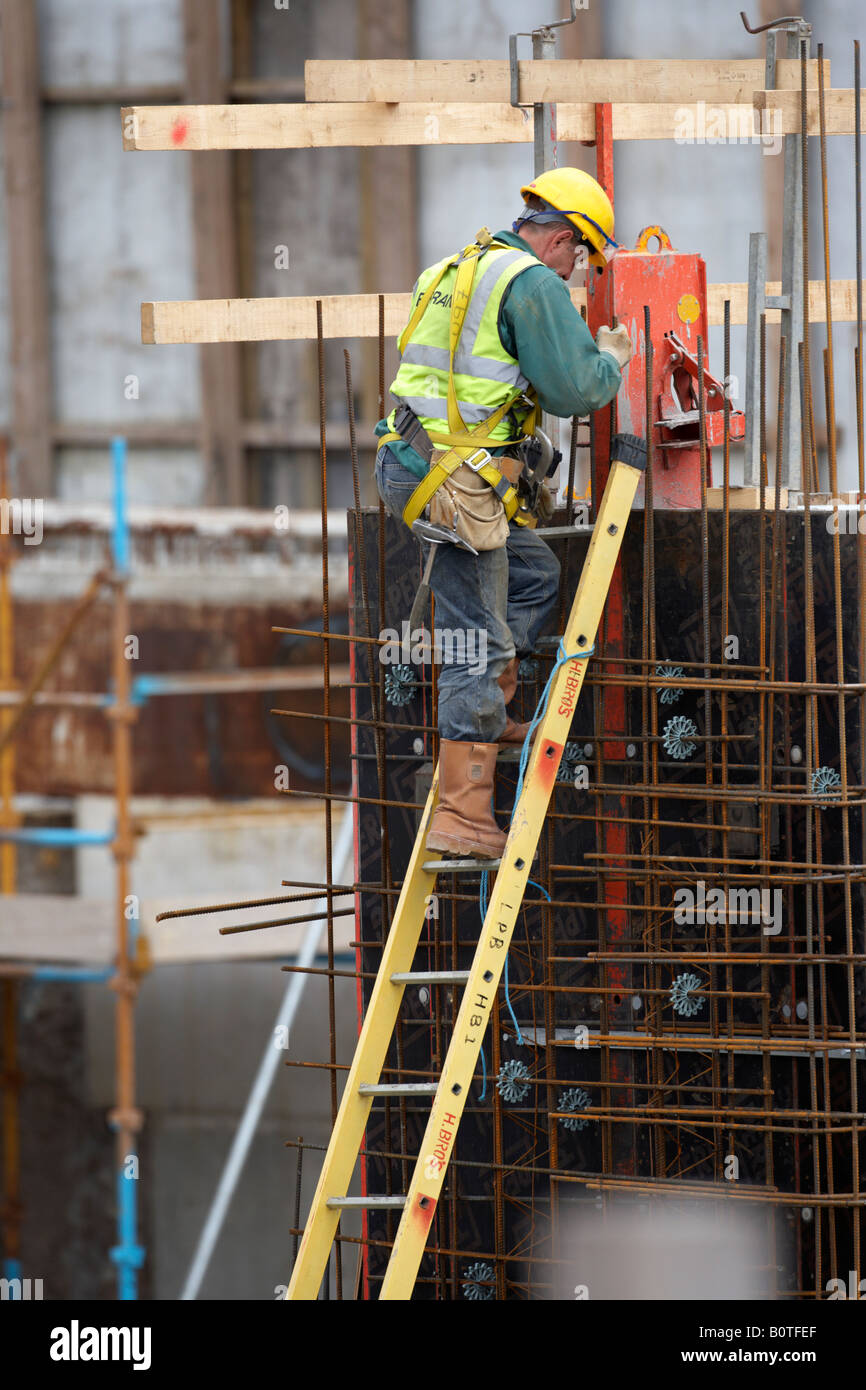 worker wearing full safety gear and harness climbing ladder on a ... for Worker Climbing Ladder  584dqh