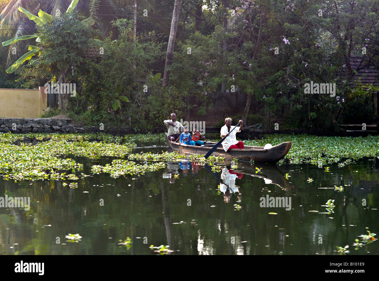 INDIA KERALA Two Indian Men And Three Boys Rowing Their Wooden Canoe Across The Canals In Backwaters Of Kerala