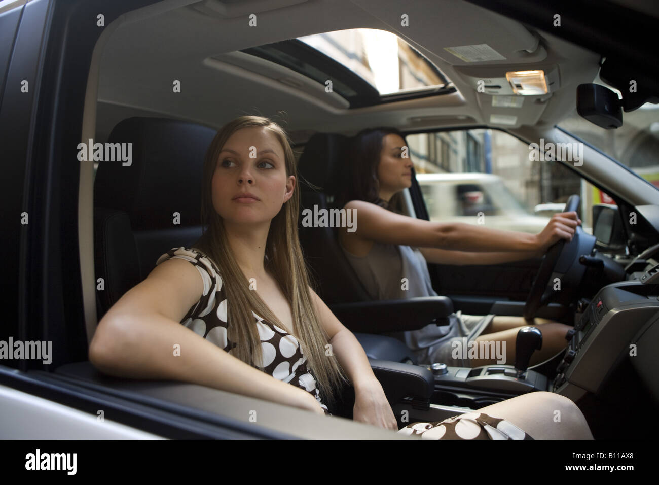 Two Young Women Driving Downtown In White Suv Stock Photo Royalty