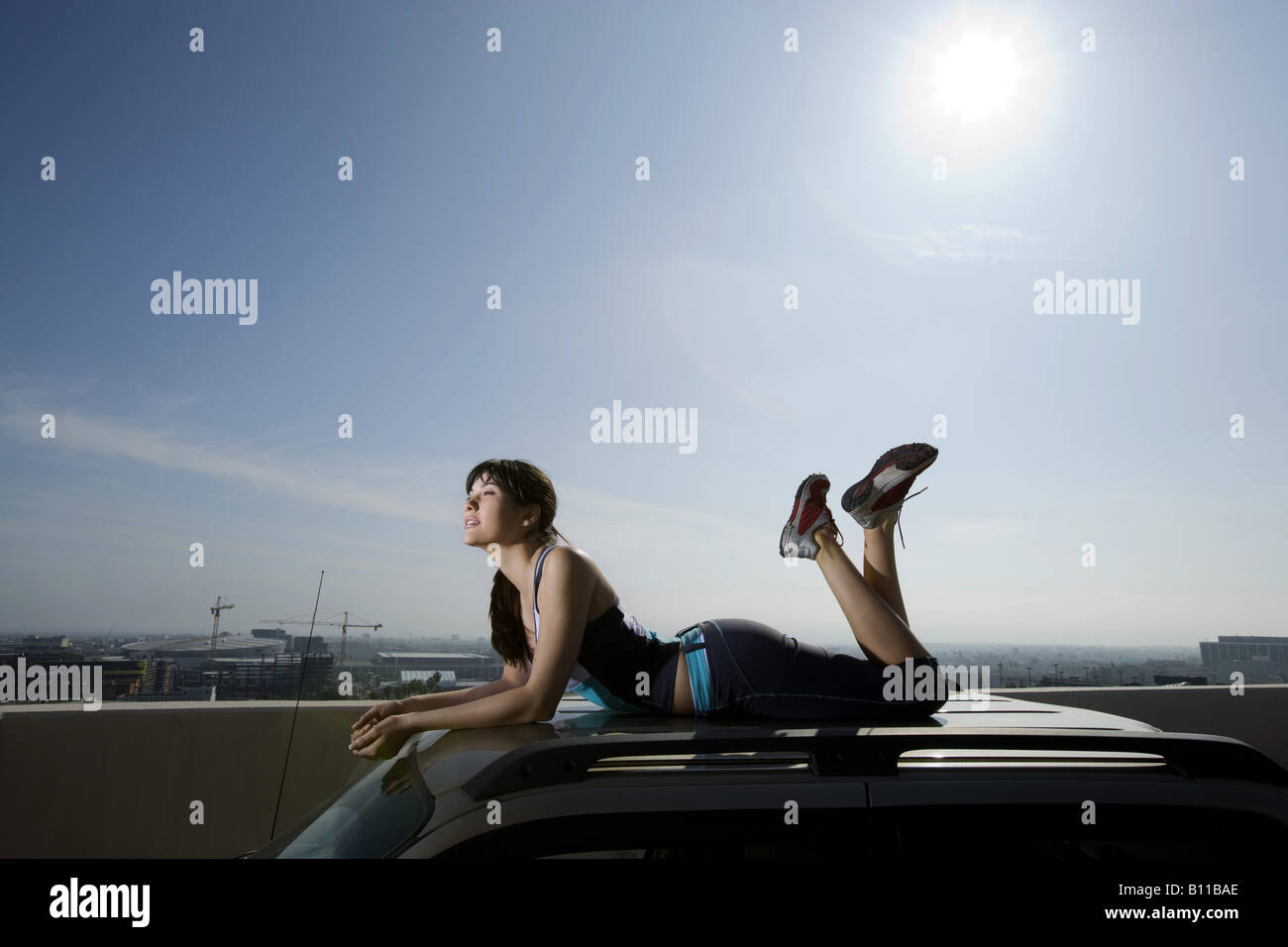 Woman Lying On Top Of Suv On Roof Top Car Park Stock Photo