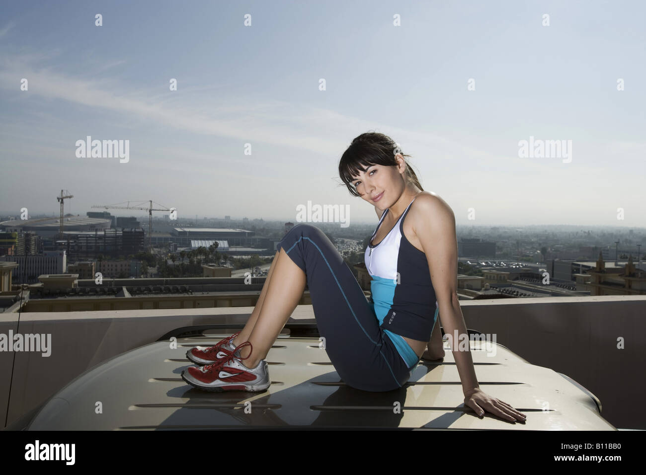 Woman Sitting On Top Of Suv On Roof Top Car Park Stock Photo