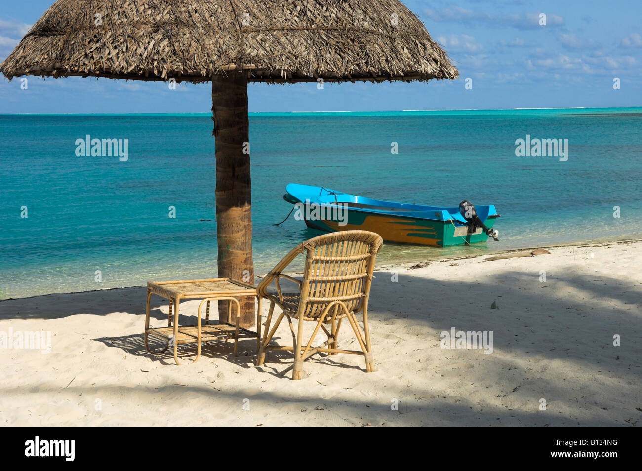 Thatched Beach Umbrella Empty Rattan Chair And Table With Boat On Tropical  Turquoise Blue Sea