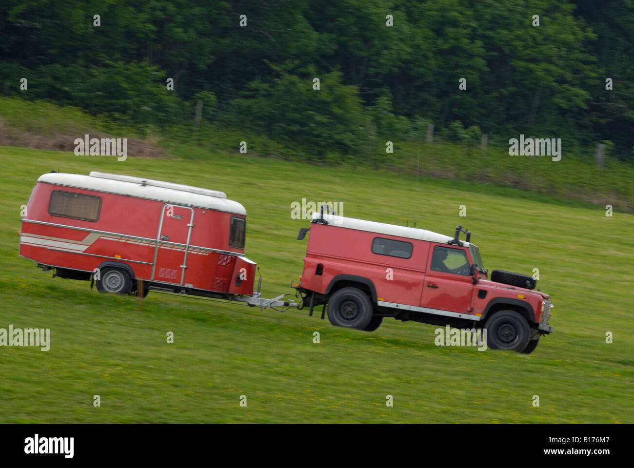 Red land rover defender 110 hard top towing a matching red for Cross country motor club towing