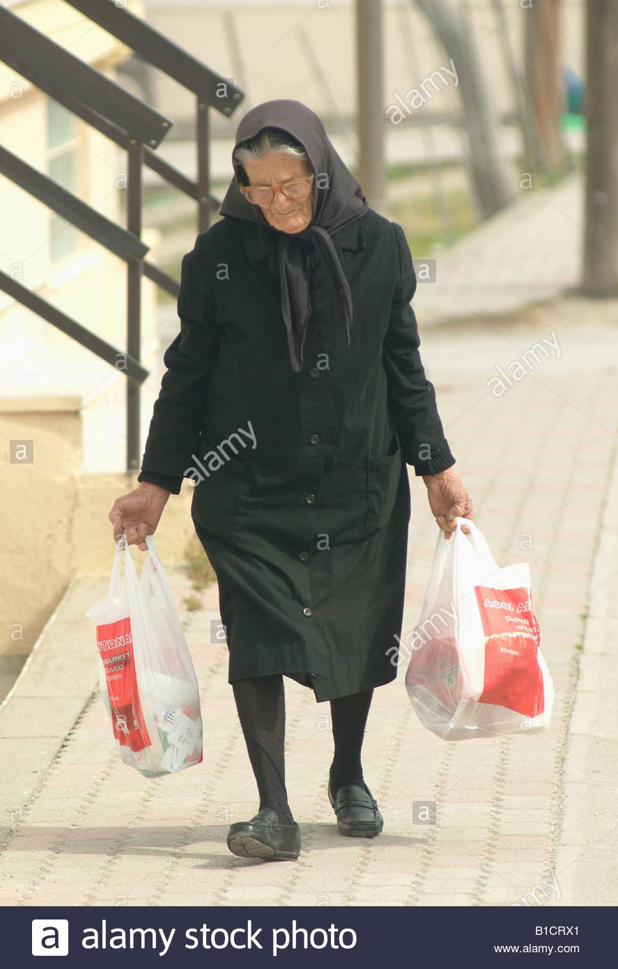 Old Greek Lady Carrying Her Shopping In Plastic Bags Greece