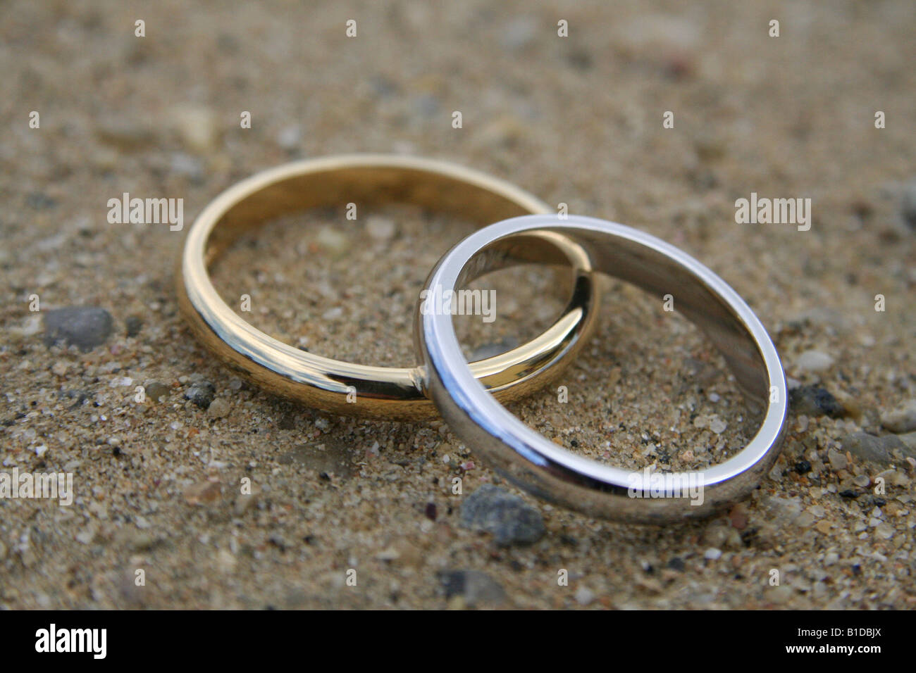 Closeup shot of two wedding rings arranged on a sandy beach Stock