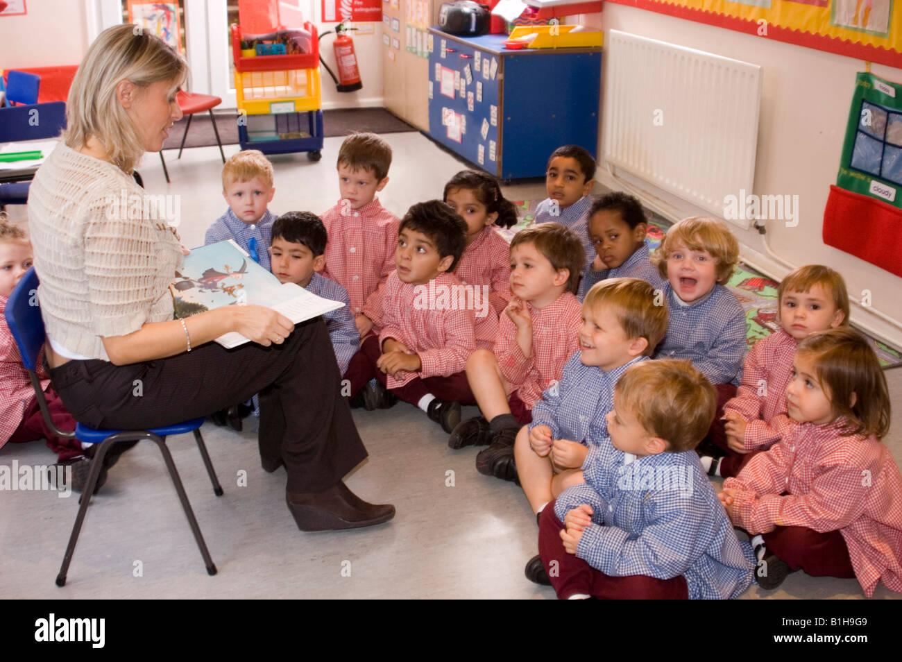 Nursery school teacher reading a story book to the class Stock ...