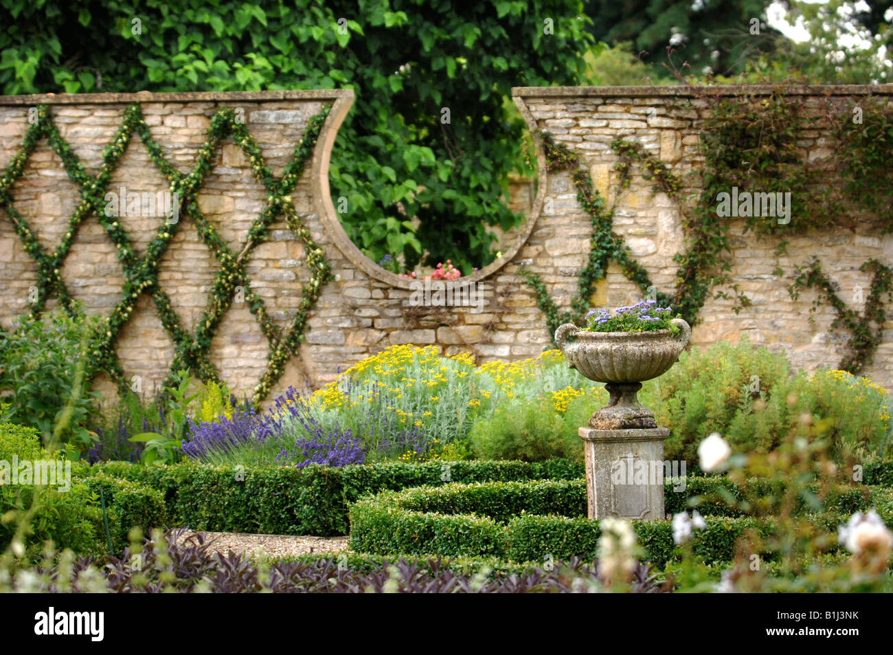 An Antique Stone Urn In A Walled Garden With Dwarf Box