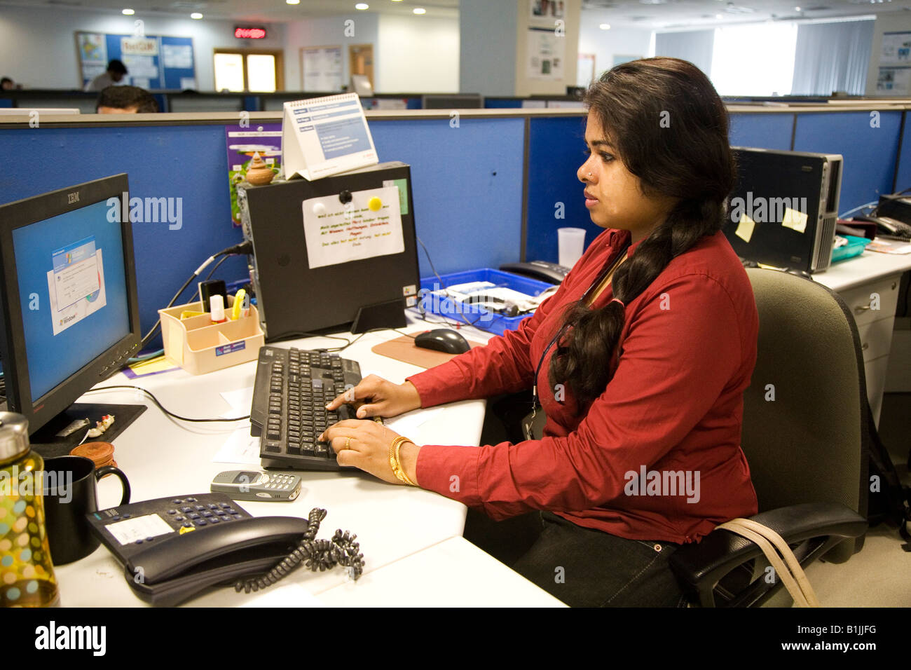 software company office. a woman works at desk in the office of company which produces software and technology driven products bangalore india