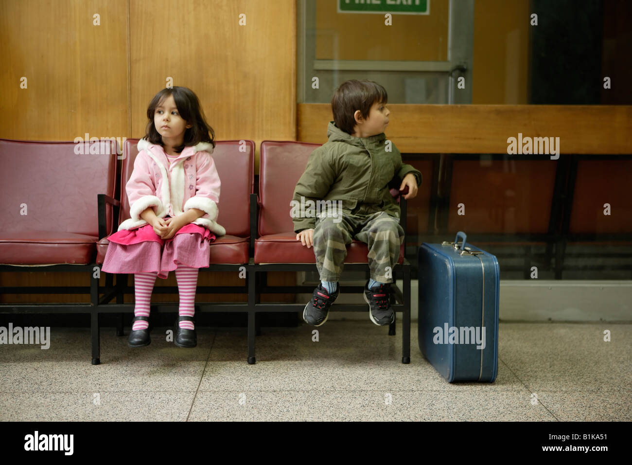 brother and sister in railway station waiting room boy aged six aged four