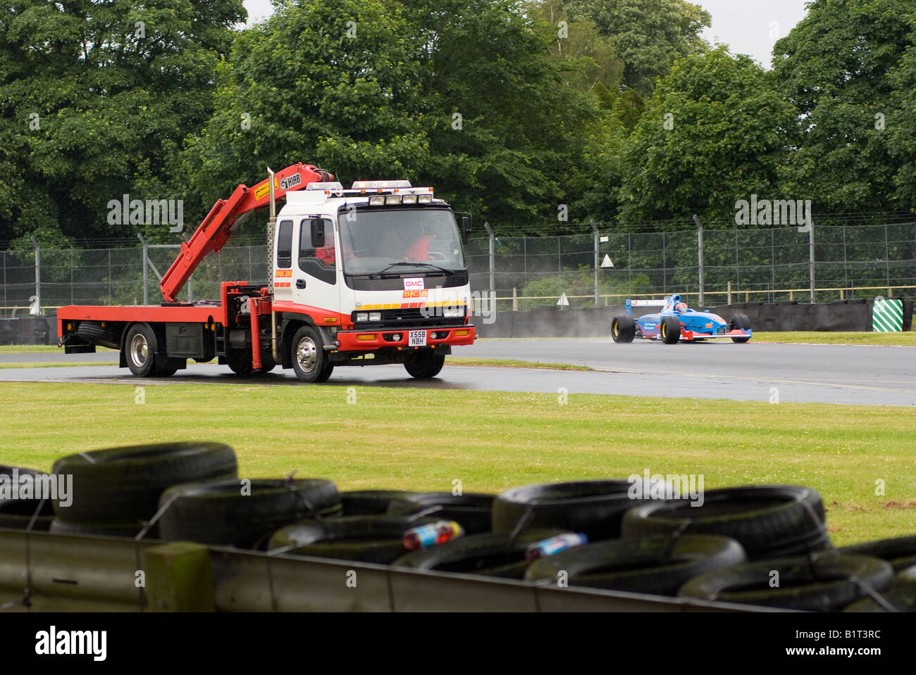 Formula palmer audi in old hall corner passes by recovery truck in pit road at oulton park motor racing circuit cheshire