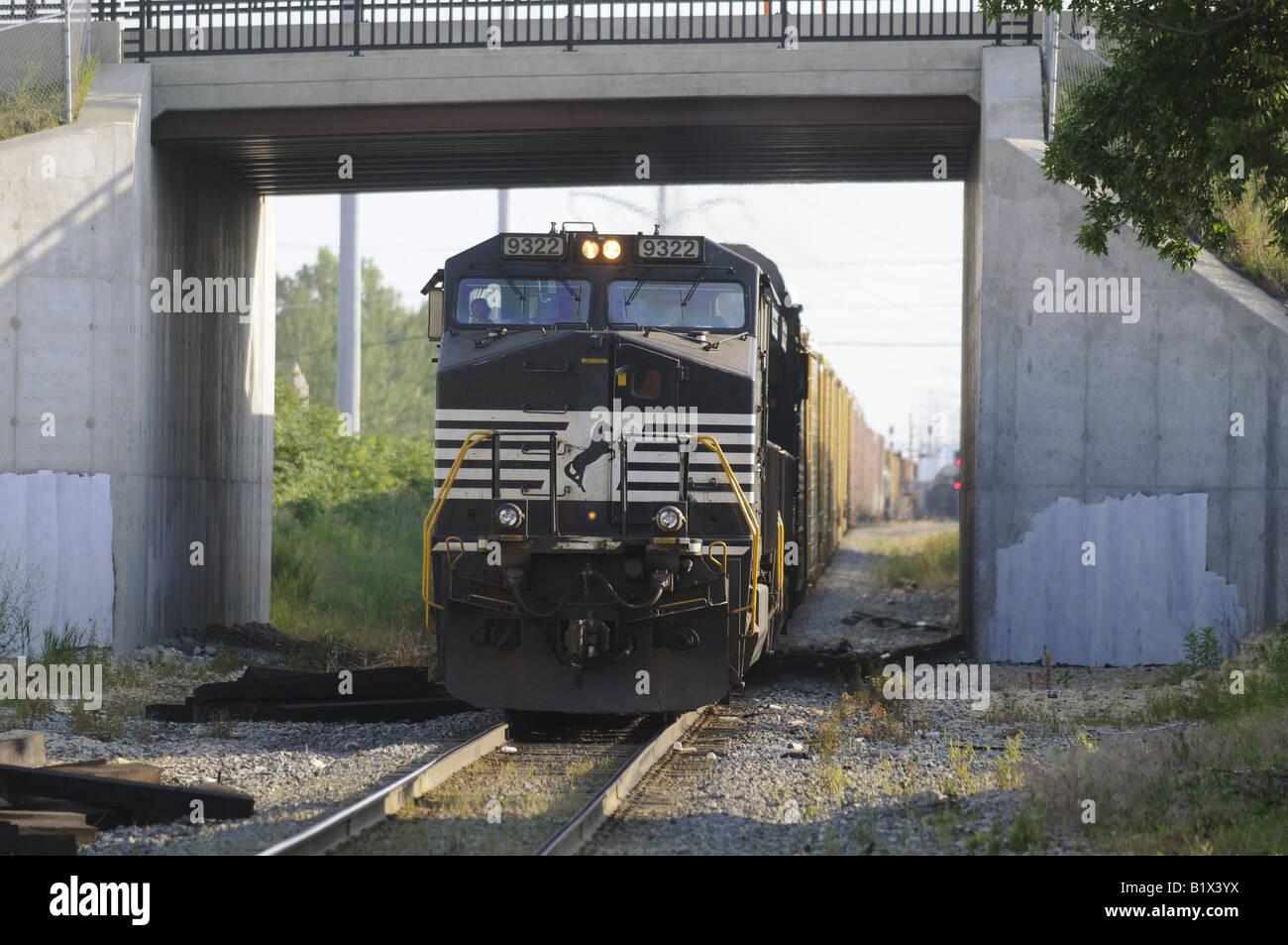 A diesel locomotive pulls a long freight train through an ...