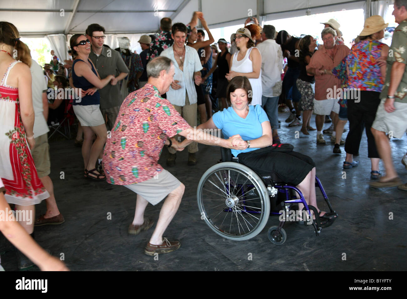 Woman in a wheelchair dancing at the Economy Hall tent at the New Orleans Jazz and Heritage Festival New Orleans LA USA & Woman in a wheelchair dancing at the Economy Hall tent at the New ...