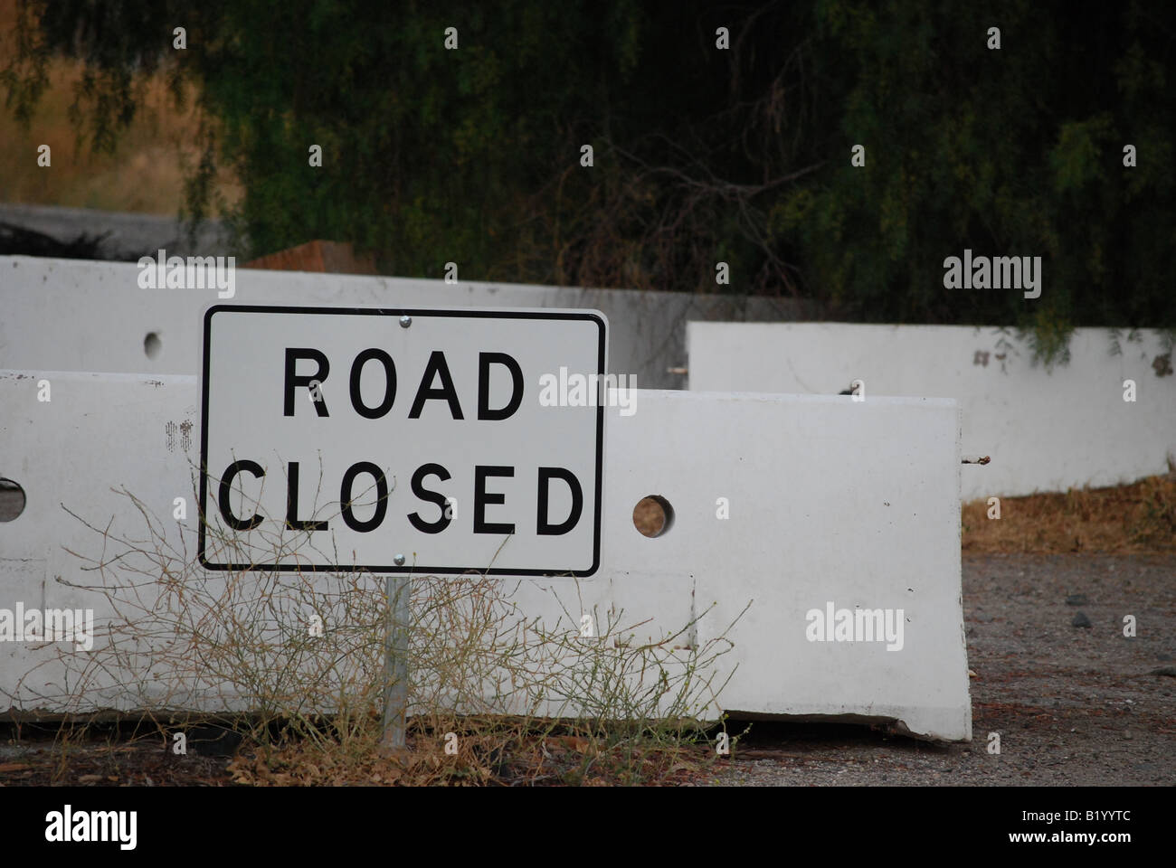 Road closed sign with concrete barriers stock photo