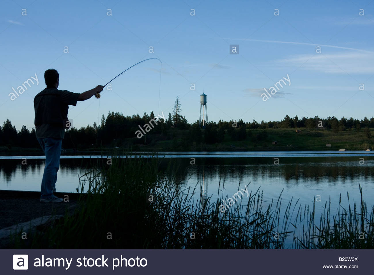 Silhouette of a man casting a fly rod from the shore at ...