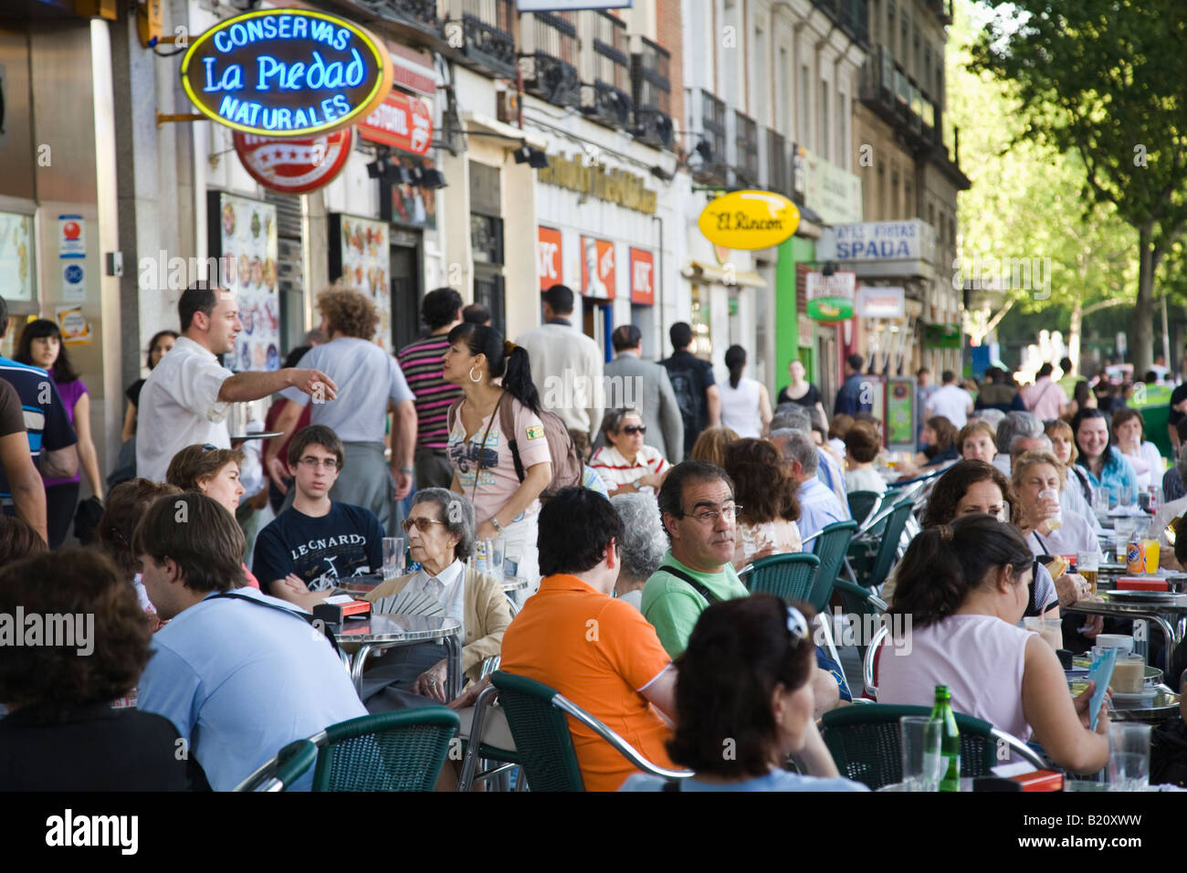 SPAIN Madrid People sit at crowded outdoor tables along ...