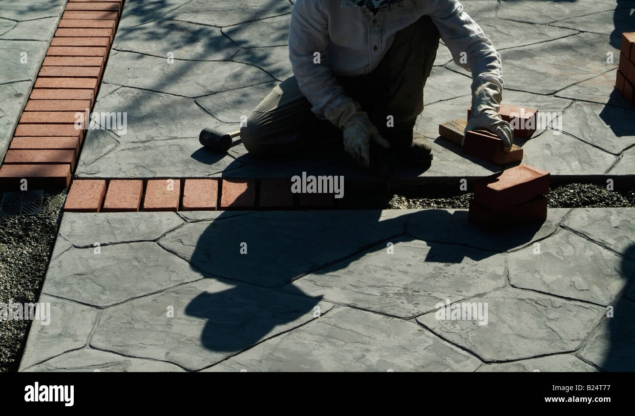 Mason Lays Red Clay Bricks Between Stamped Concrete Slabs Finishing A New Patio  In The Backyard Part 39