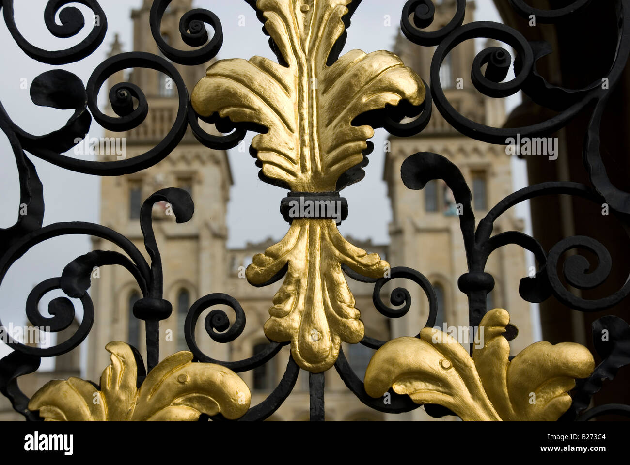 golden scroll decoration on wrought iron gate and two towers