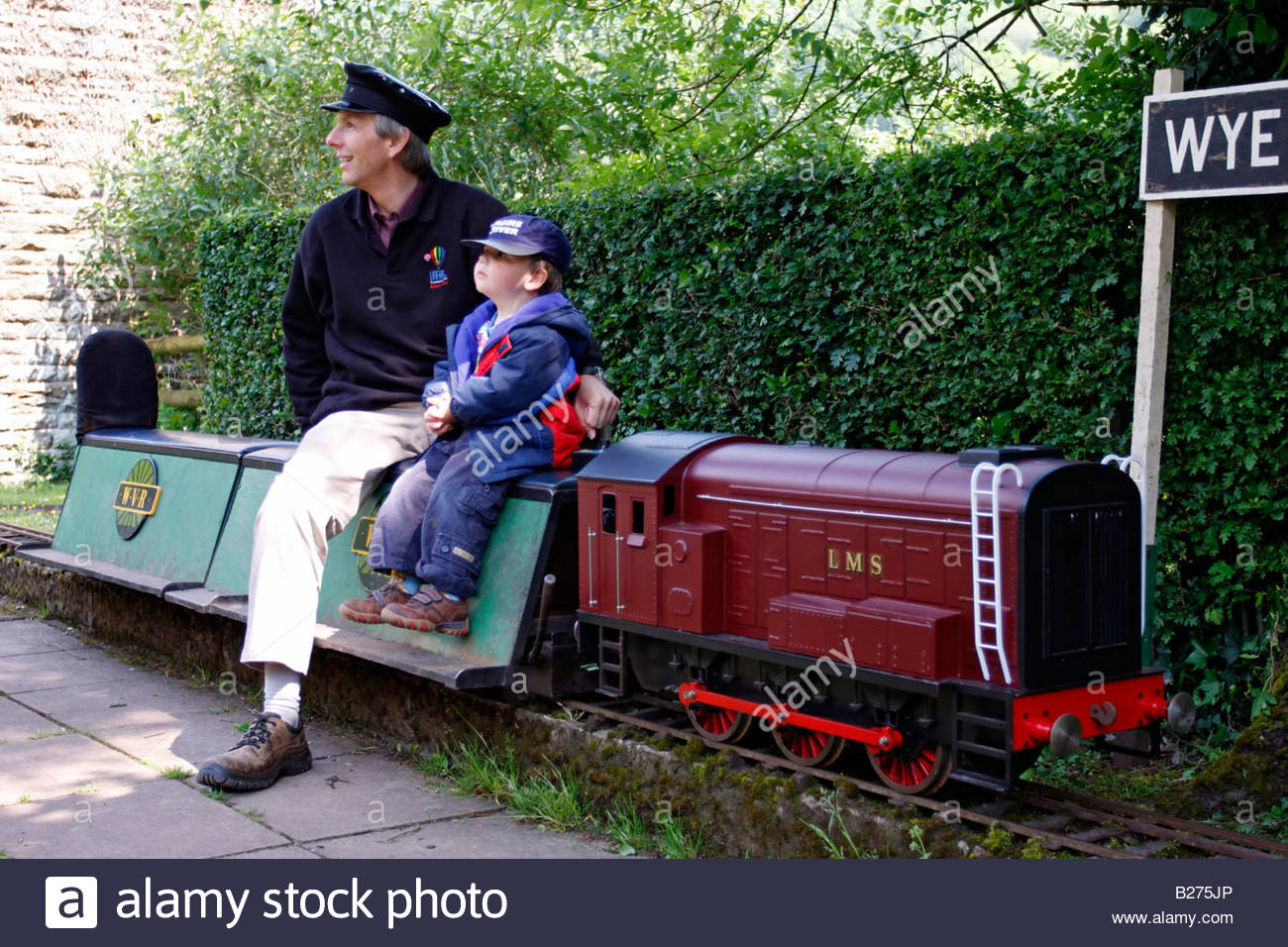 engine driver with little boy sitting on miniature model gwr