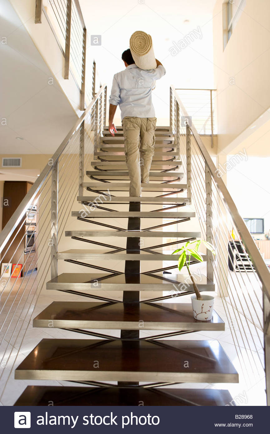 Man Carrying Rolled Carpet Up Stairs In New Home