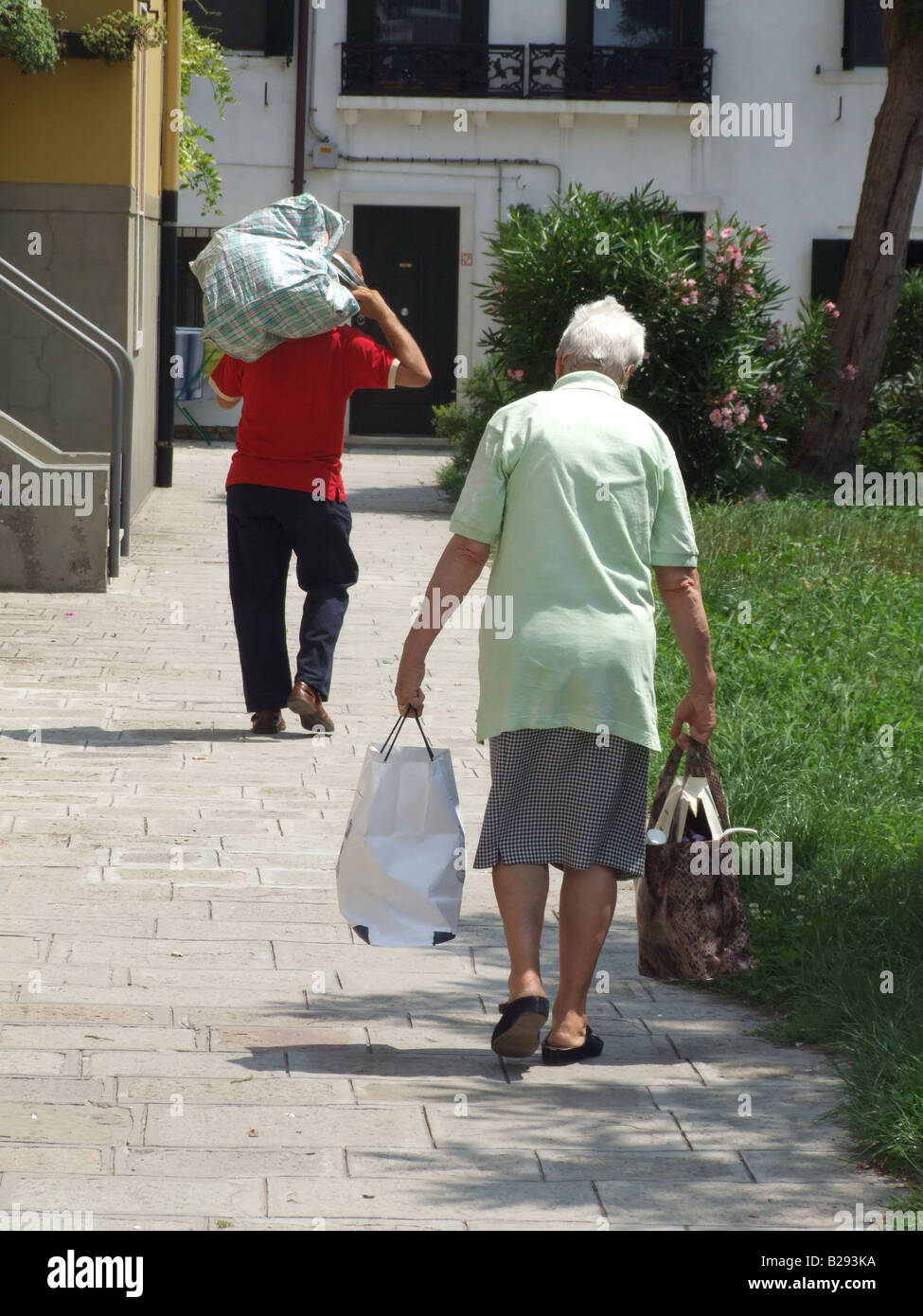 Elderly couple carrying heavy shopping bags venice stock