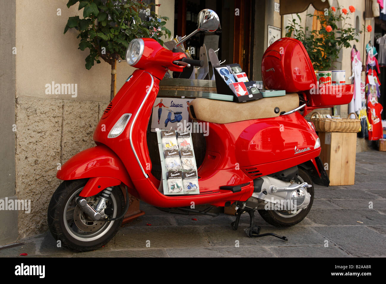 red piaggio vespa outside a shop along via roma radda in chianti