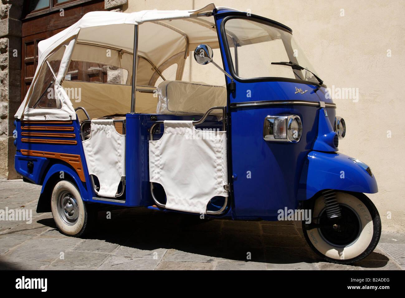 blue piaggio ape calessino outside a shop along via roma radda in