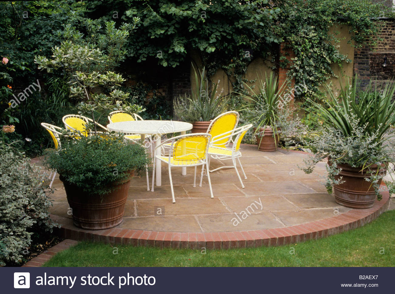 Stock Photo   Private Garden London Circular Brick And Stone Patio Area  With Table And Chairs At Bottom Of Garden