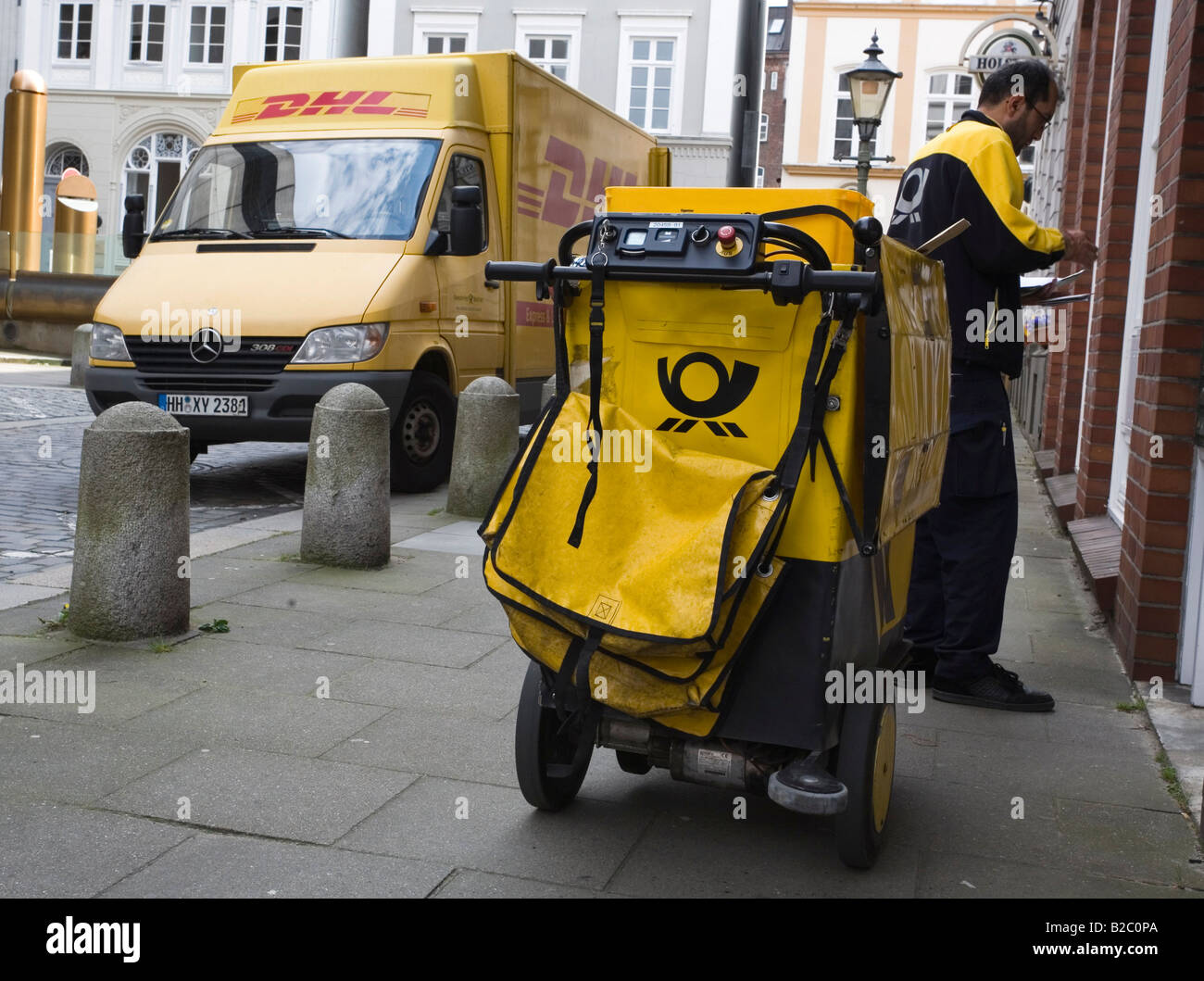 postman with his dhl motorised deliver cart in the city centre of stock photo royalty free. Black Bedroom Furniture Sets. Home Design Ideas