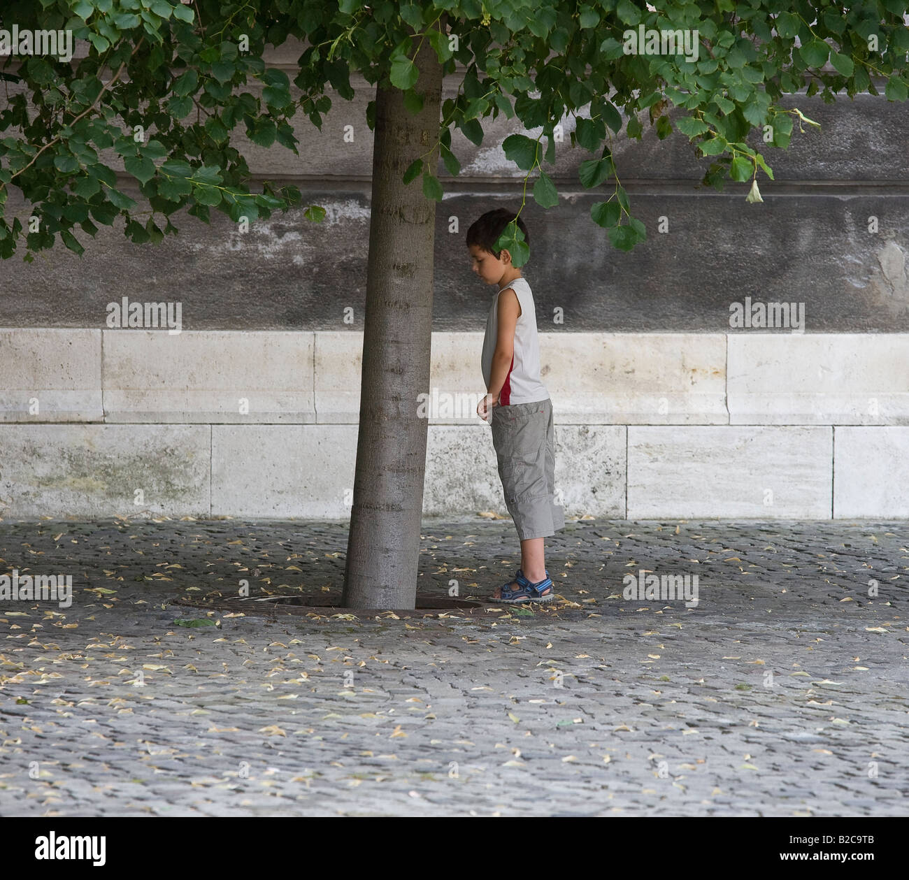 India child Pissing boy pissing against tree - Stock Image