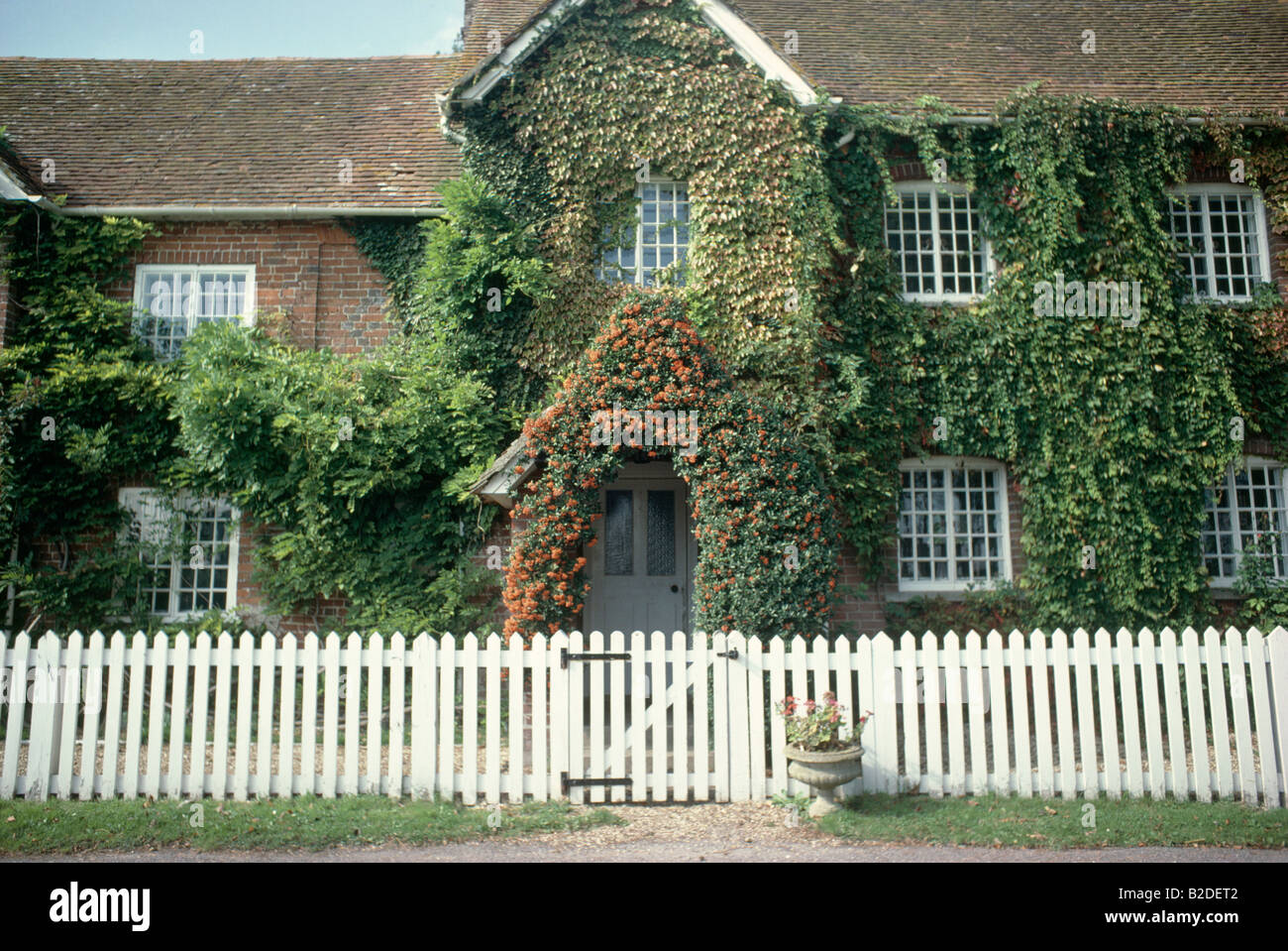 White Picket Fence In Front Of Traditional Old House With