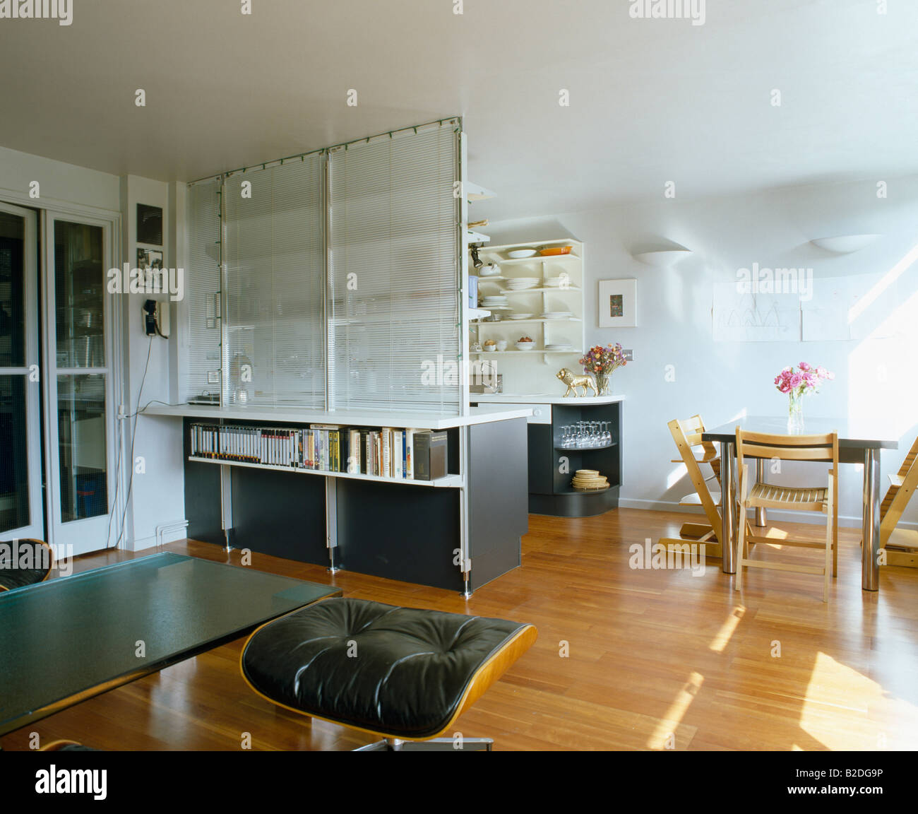 Wooden flooring and white dividing screen in open plan kitchen and ...