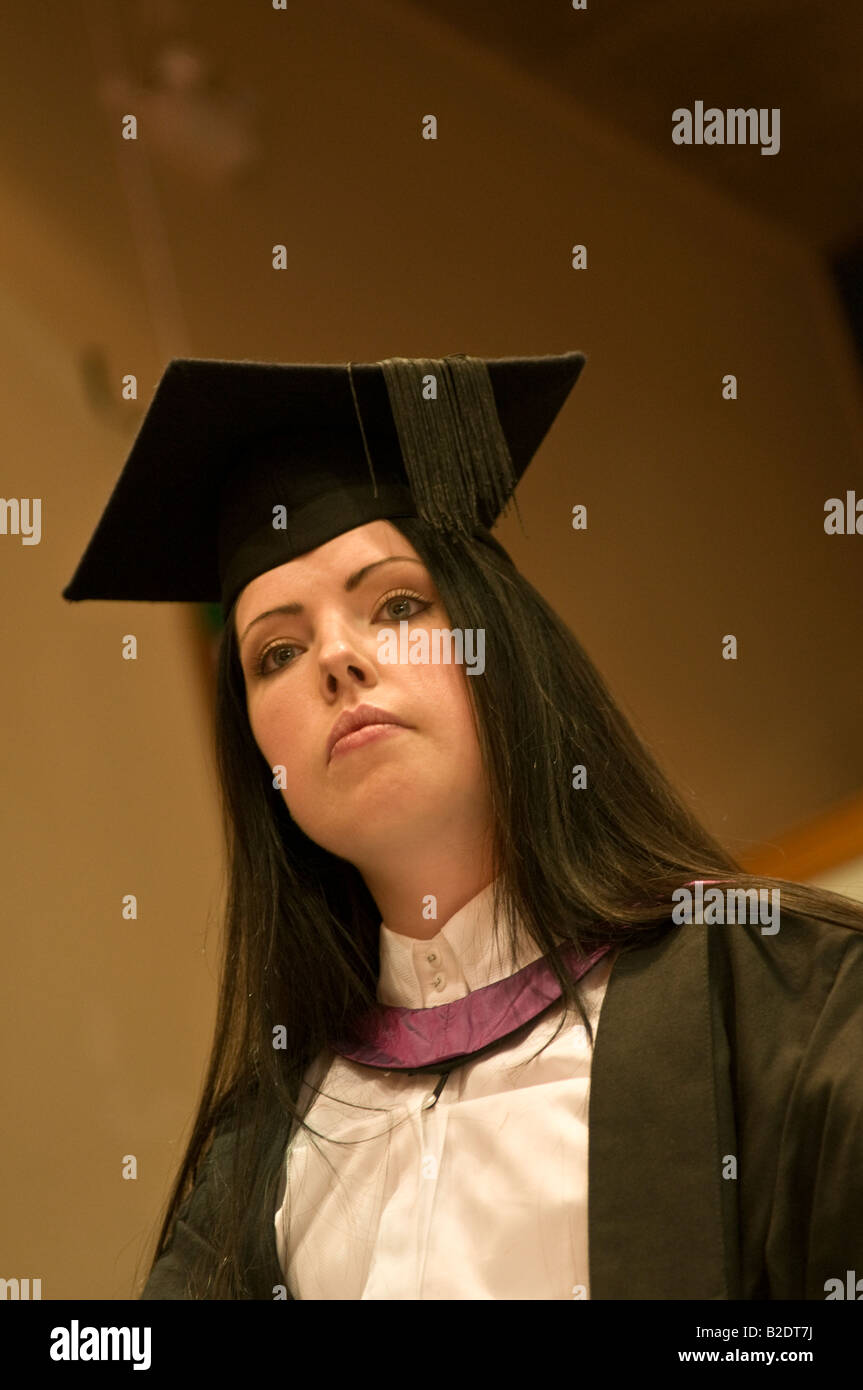 looking up at woman student wearing mortar board and gown at Stock ...