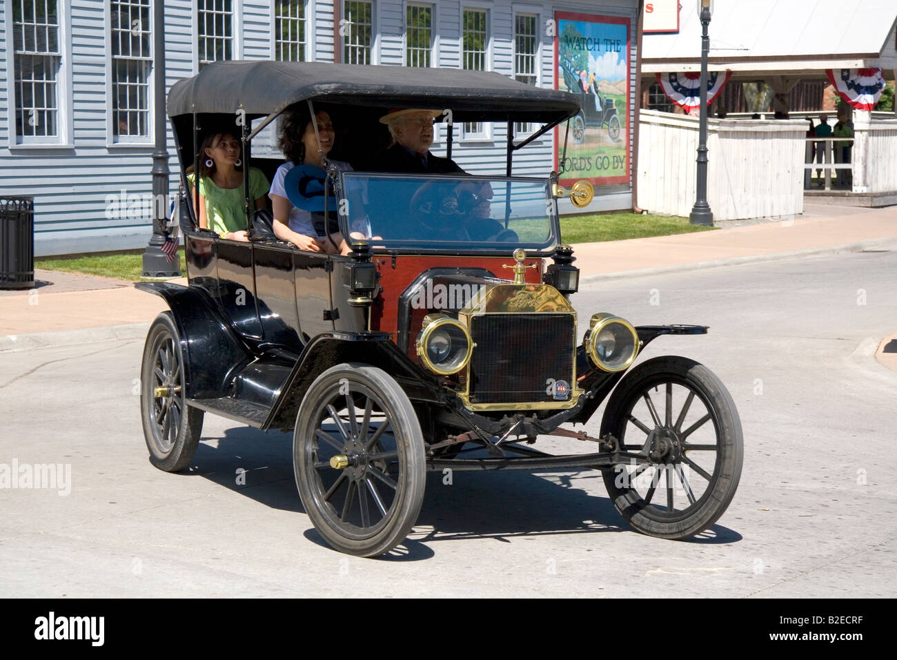 Visitors ride in a ford model t on the streets of greenfield village at the henry