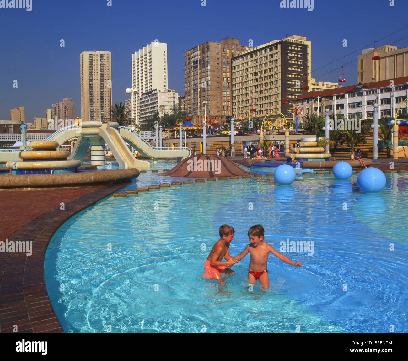 Two small kids paddling in the beachfront paddling pools for Small paddling pool
