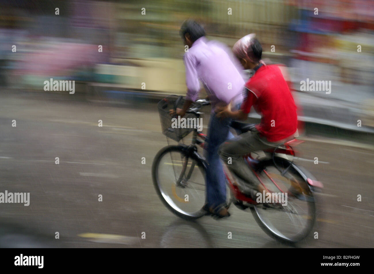Indian Man Couple Bicycle Riding Bike At Street In Delhi In Heavy