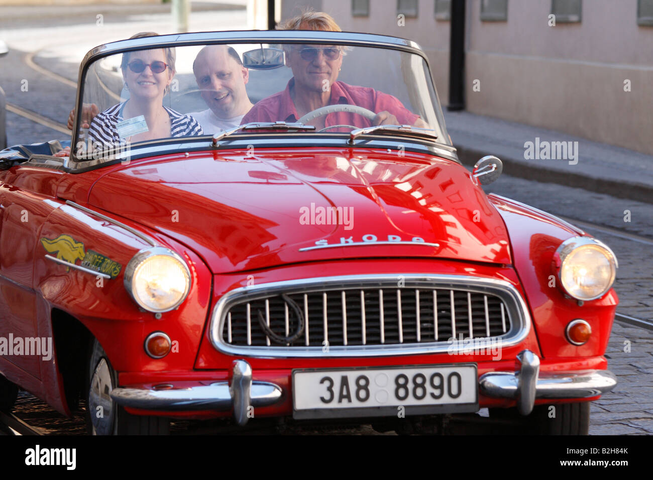 Old classic model of red convertible Czech Skoda with tourists and ...