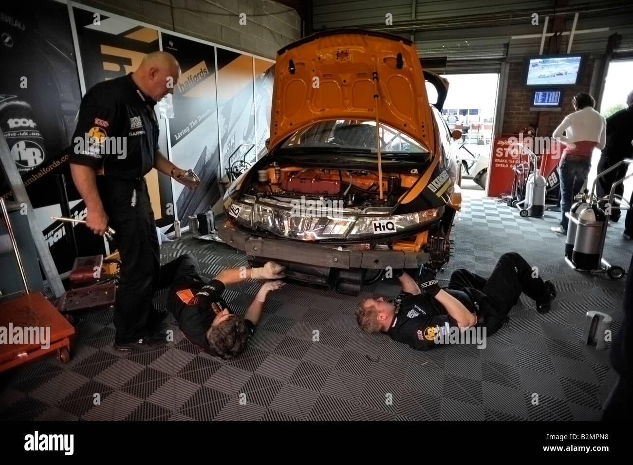 Race Mechanics Working On Honda Car In Team Dynamics Garage