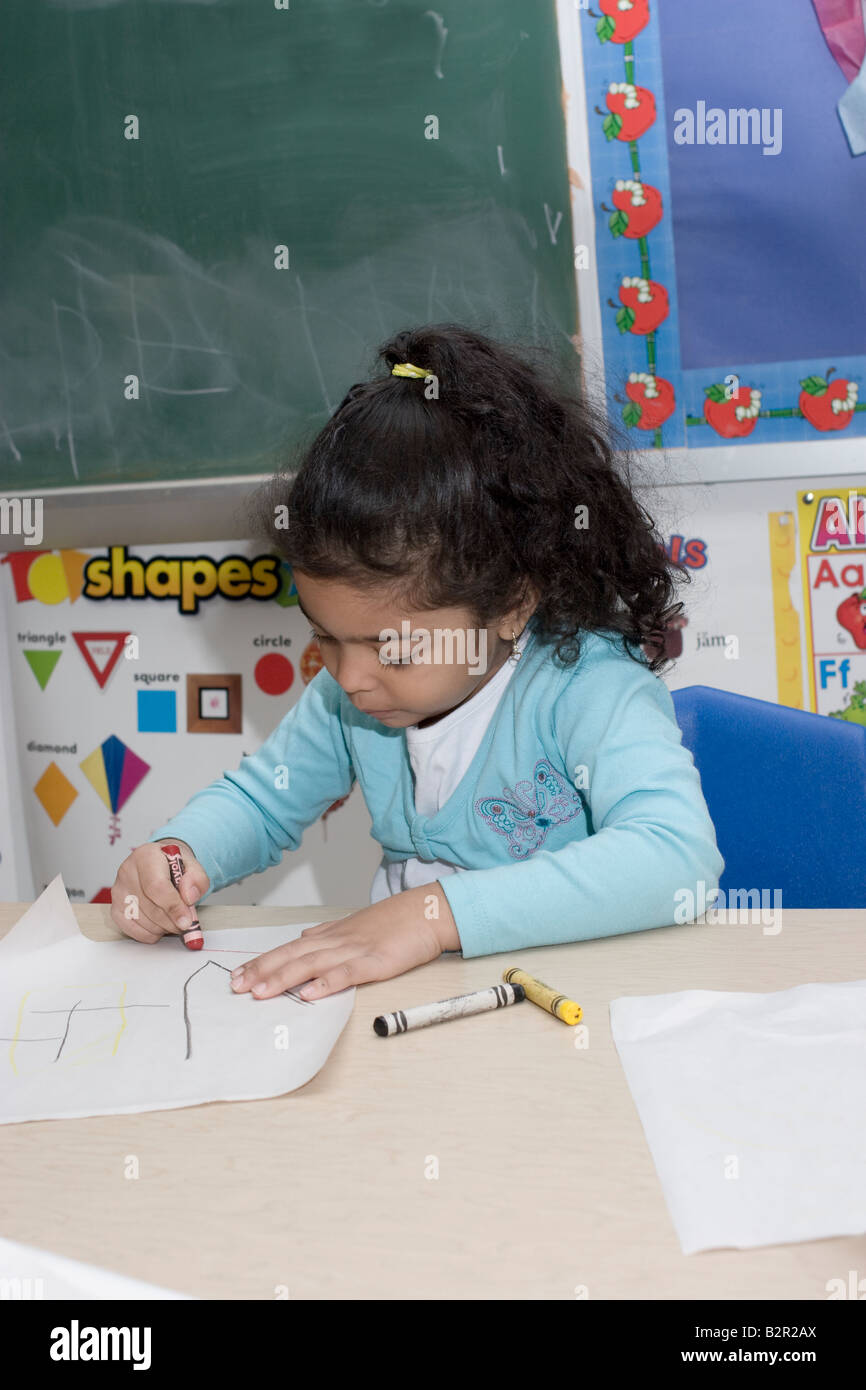 4 year old preschool girl sitting at a table coloring Stock Photo ...